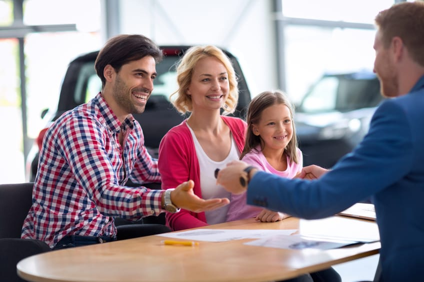 family buying a new car from a dealer