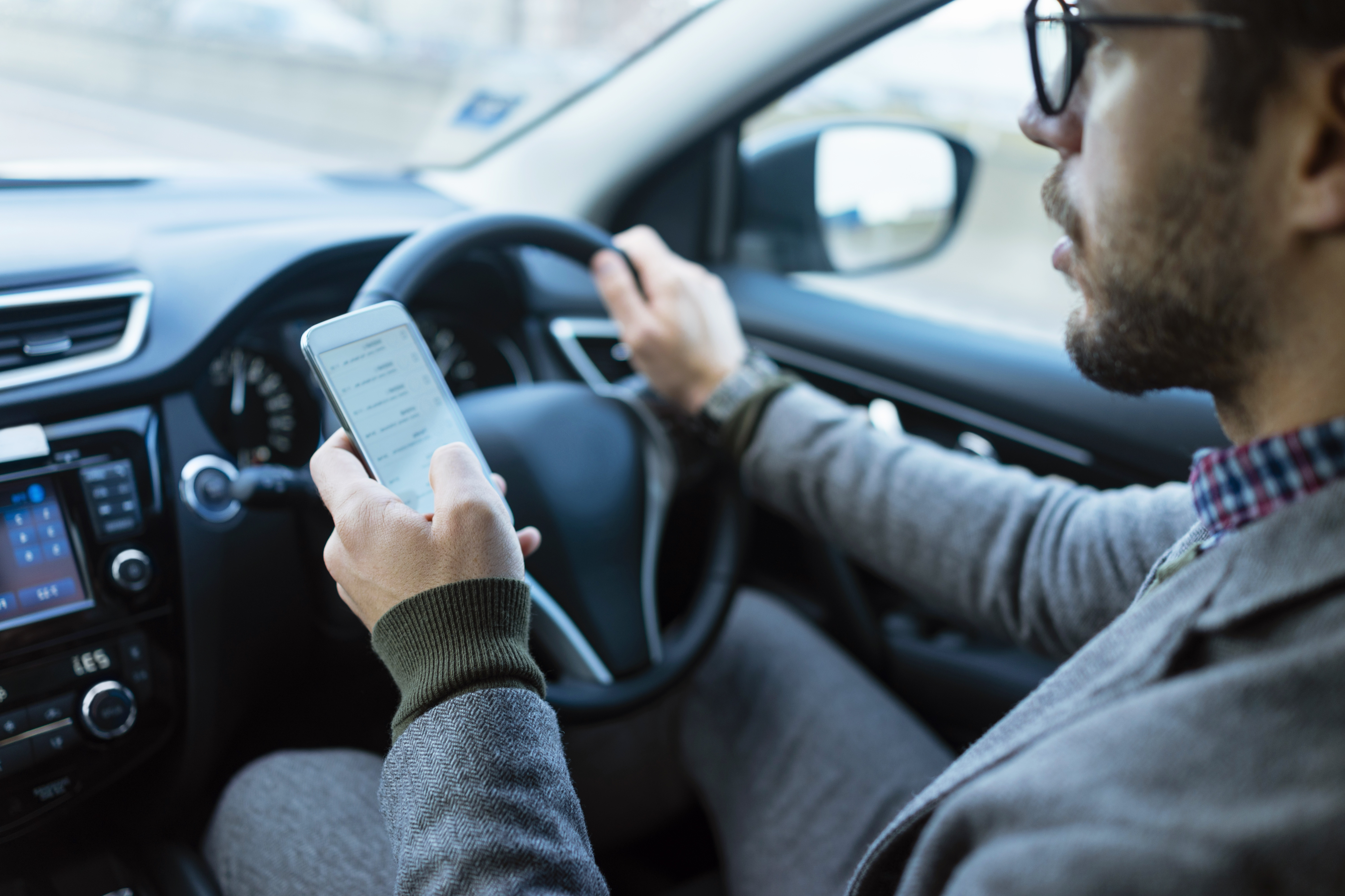 businessman using mobile phone while driving