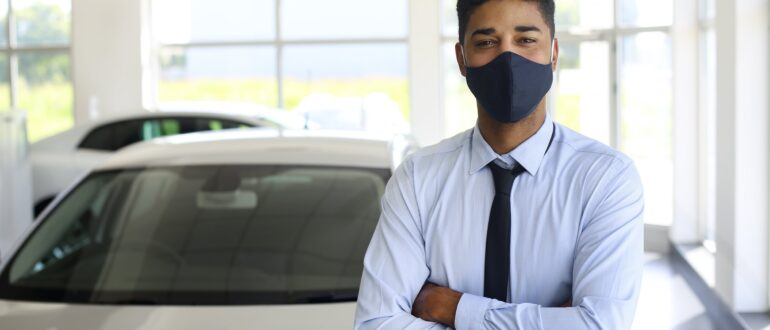 man standing crossed arms wearing mask in a car dealership