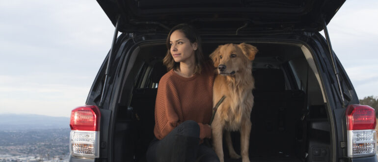 Young woman sitting in the back of her SUV with her golden retriever