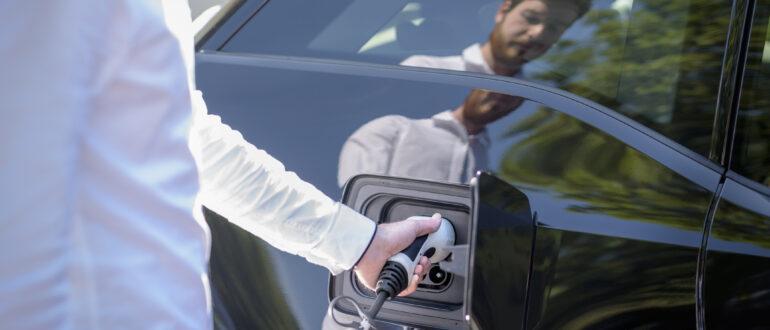 Man charging electric vehicle